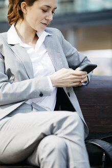 Young businesswoman sitting on a bench in the city, using smartphone - JRFF03051
