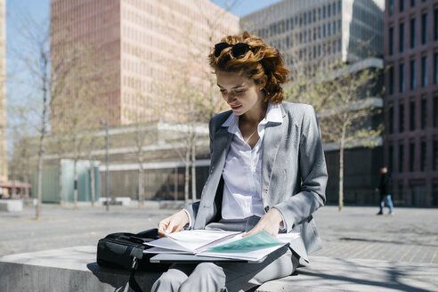 Young businesswoman reading documents, sitting on a bench in the city on a sunny day - JRFF03069