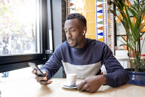 Young man with wireless earphones  in a coffee shop looking at cell phone - OCMF00399