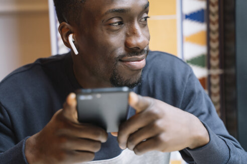 Close-up african man with mobile phone and headphones. - OCMF00405