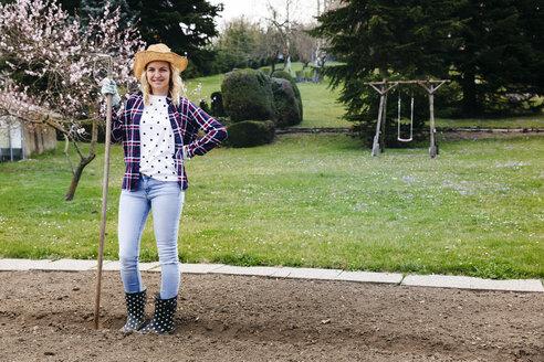 Young woman raking - HMEF00299