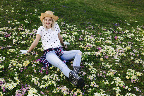 Young woman is sitting in flower meadow - HMEF00326