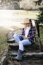 Young woman with straw hat working outdoor with her tablet - HMEF00332