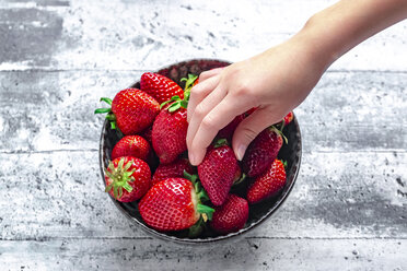 Bowl with fresh strawberries, hand of a girl - SARF04230
