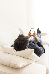 Back view of young man lying on the couch at home using smartphone - TCF06076
