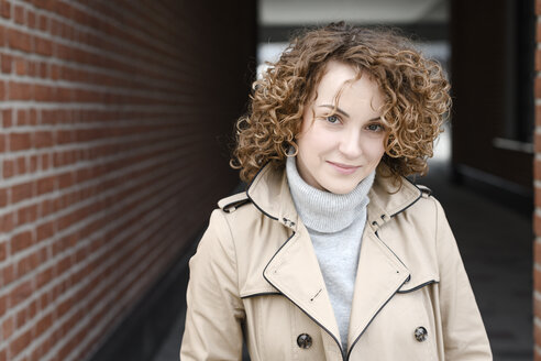 Portrait of smiling woman with curly hair wearing beige trenchcoat and turtleneck pullover - EYAF00145