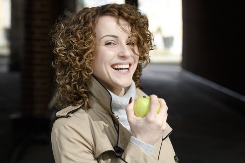 Portrait of laughing woman with curly hair with green apple - EYAF00148