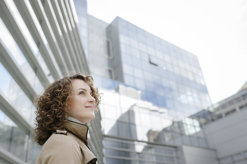 Smiling woman with curly hair in front of modern architecture looking up - EYAF00151