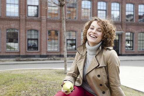 Portrait of happy woman with curly hair sitting on a meadow eating an apple - EYAF00154