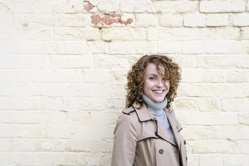 Portrait of young curly woman in trench coat near yellow wall - EYAF00160