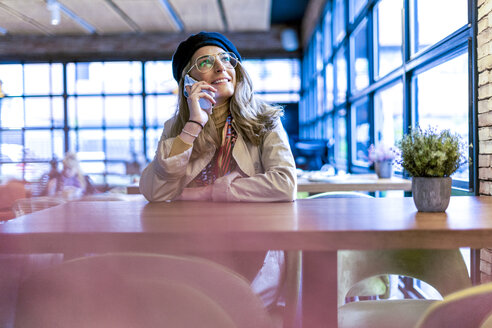 Smiling woman on cell phone in a cafe - ERRF01064