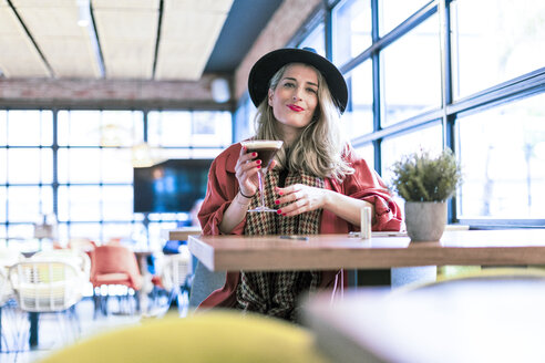 Portrait of woman drinking a coffee cocktail in a cafe - ERRF01073