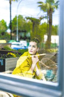 Woman behind windowpane in a cafe - ERRF01100
