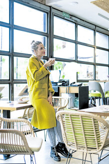 Woman drinking coffee at the window in a cafe - ERRF01109