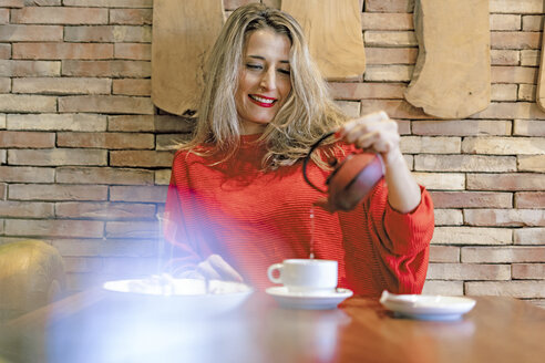 Smiling woman pouring tea into cup in a cafe - ERRF01112