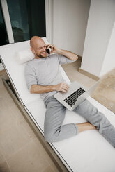 Happy man lying on lounge using cell phone and laptop - LHPF00526