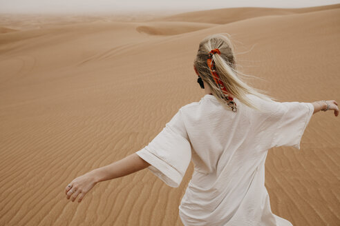 United Arab Emirates, Dubai, Lahbab Desert, woman walking in desert landscape - LHPF00529