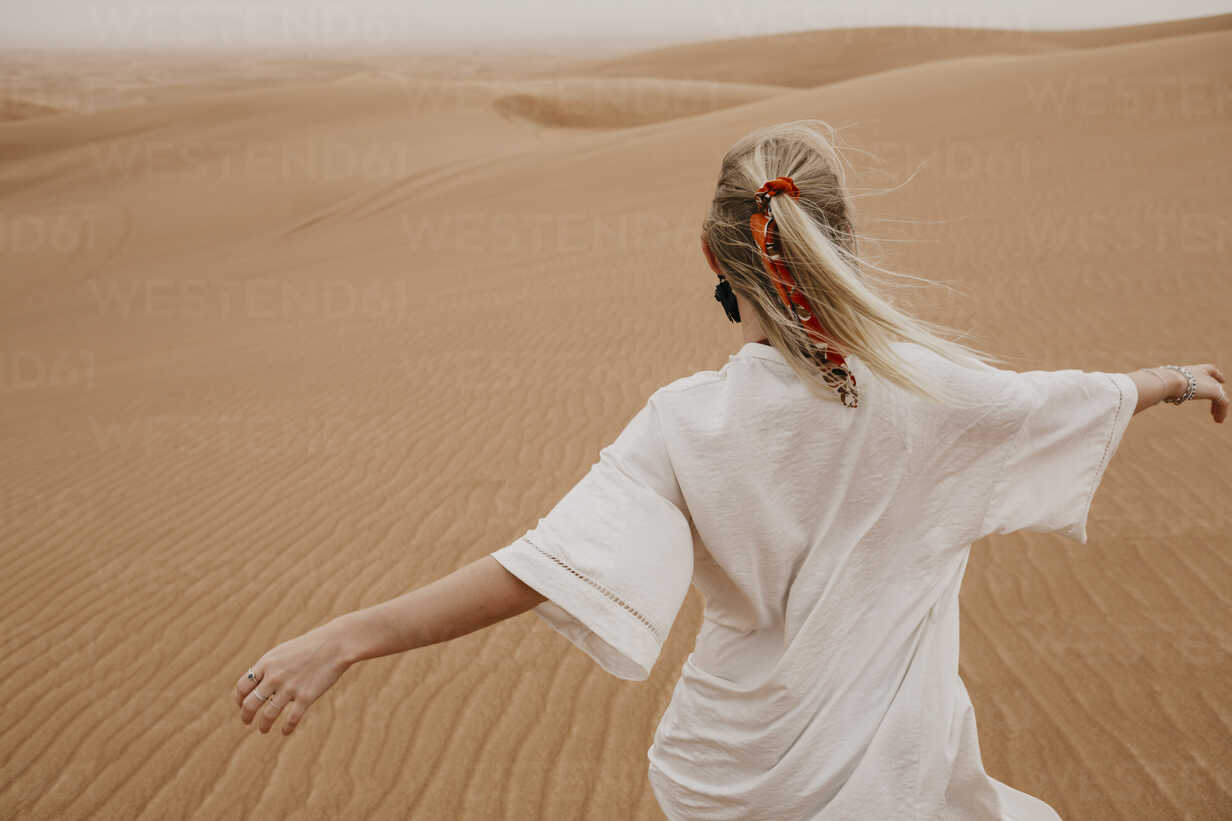 United Arab Emirates, Dubai, Lahbab Desert, woman walking in desert landscape - LHPF00529 - letizia haessig photography/Westend61