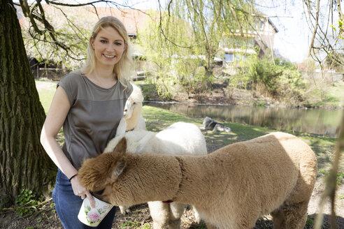 Portrait of happy woman feeding alpacas - FLLF00101