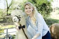 Portrait of smiling woman with white  alpaca wearing bridle and bow tie - FLLF00110