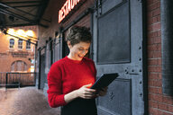 Germany, Berlin, smiling restaurant manager using digital tablet outdoors - TAMF01275
