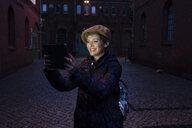 Germany, Berlin, portrait of happy tourist taking selfie with digital tablet - TAMF01284
