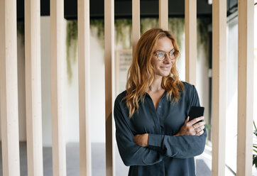 Smiling businesswoman holding cell phone looking sideways - GUSF01862