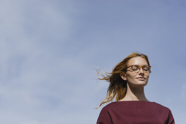Portrait of young woman with glasses and closed eyes under blue sky - GUSF01886