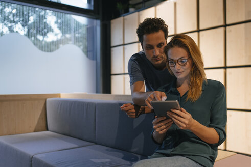 Young man and woman sharing tablet on couch - GUSF01889