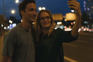 Smiling young couple taking a selfie in the city at night - GUSF01898