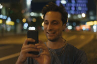 Smiling young man using cell phone in the city at night - GUSF01904