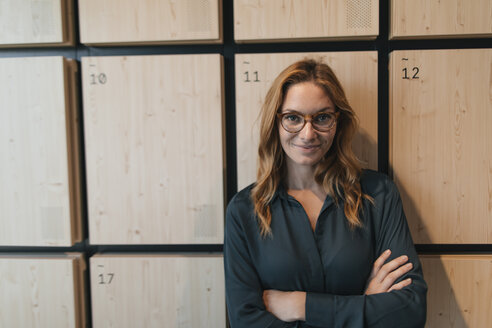 Portrait of confident businesswoman standing at lockers - GUSF01910