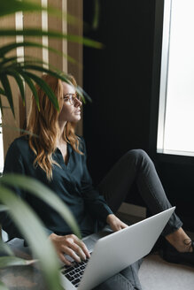 Businesswoman sitting on the floor using laptop - GUSF01913