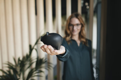 Businesswoman holding piggy bank - GUSF01916