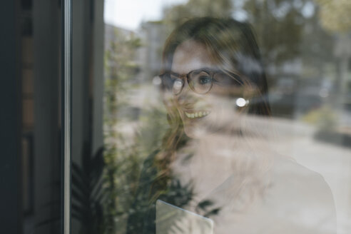 Smiling businesswoman behind windowpane - GUSF01925