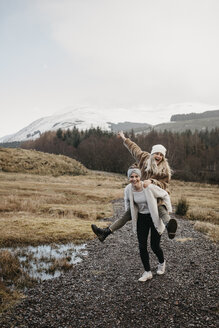 UK, Scotland, happy young woman carrying friend piggyback in rural landscape - LHPF00544