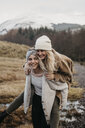 UK, Scotland, happy young woman carrying friend piggyback in rural landscape - LHPF00547
