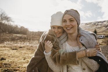 UK, Scotland, happy female friends hugging in rural landscape - LHPF00553