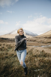 UK, Scotland, Loch Lomond and the Trossachs National Park, happy young woman running in rural landscape - LHPF00562