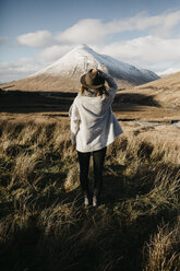 UK, Scotland, Loch Lomond and the Trossachs National Park, rear view of young woman standing in rural landscape looking at mountain - LHPF00565