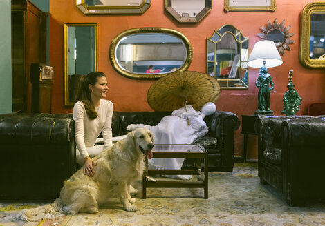 Smiling woman with dog sitting on couch in a vintage shop - MGOF04008