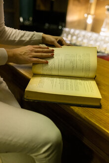 Close-up of woman reading an old book in a vintage shop - MGOF04014
