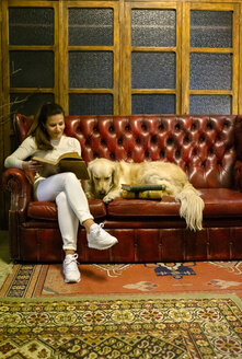 Woman with dog sitting on couch in a vintage shop reading an old book - MGOF04017