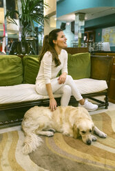 Happy woman with dog sitting on couch in a vintage shop - MGOF04023