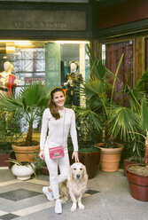 Portrait of smiling woman with dog leaving a vintage shop - MGOF04029
