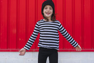 Portrait of happy little girl wearing striped shirt and black cap - ERRF01158