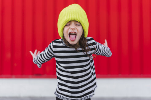 Portrait of little girl wearing striped shirt and yellow cap sticking out tongue in front of red background - ERRF01170