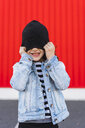 Laughing little girl covering eyes with her black cap - ERRF01179