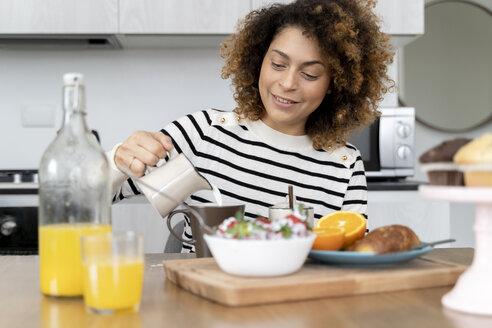 Woman sitting in kitchen, having breakfast - FMOF00587