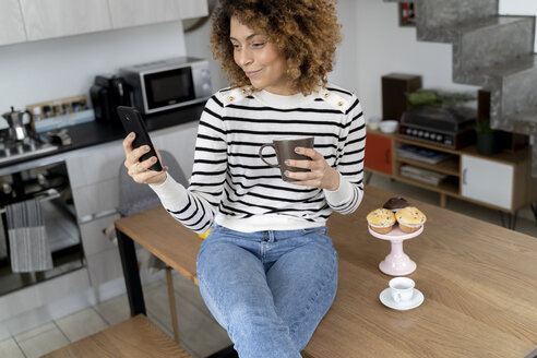 Woman sitting at home, using smartphone, eating muffin - FMOF00590